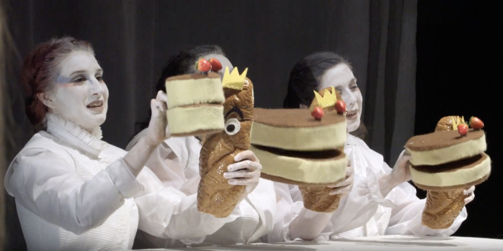 Three female Curtin actors, dressed in white, with their faces painted white, holding cakes. - play video