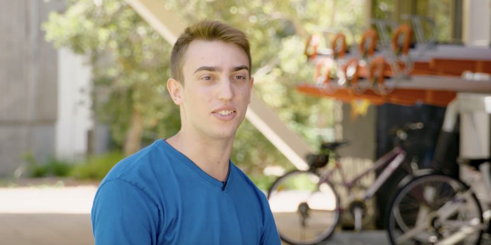 A male student, wearing a blue shirt, looking at the camera and smiling, with a bike in the background - play video