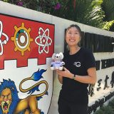 Curtin student, Lee Bing Tan holding a koala teddy and looking at camera and smiling