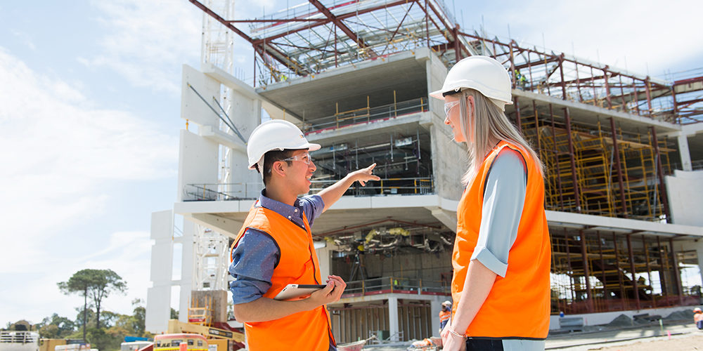 A male and female student standing in front of the Curtin medical centre that is being built