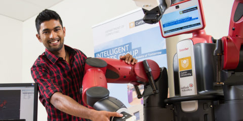 A male research student working on a robot