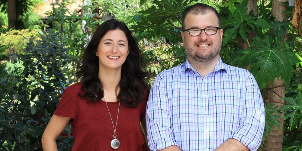 Curtin staff members, Lauren and Damian standing in front of Curtin trees, looking at camera and smiling - play video