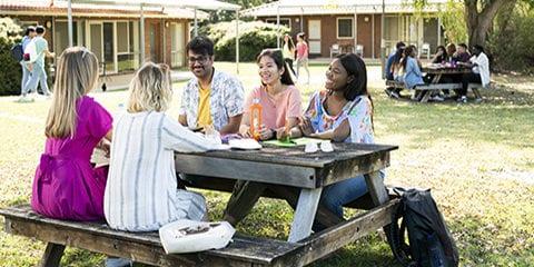 Group of students sitting outside Kurrajong Village.
