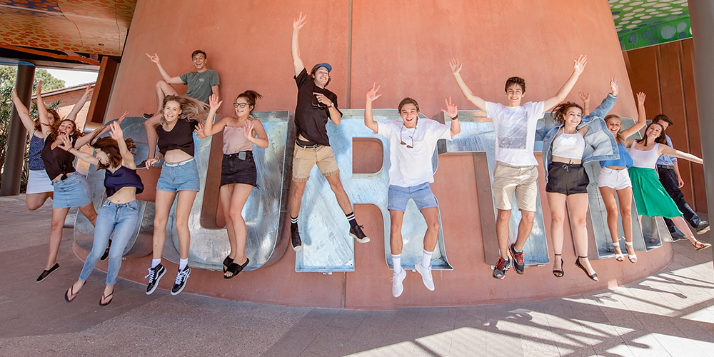 Students leaping in air and smiling in front of Curtin cookie cutter sculpture - play video