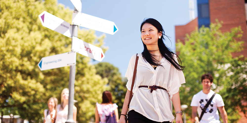 A female walking through the grounds at Curtin with a signpost in the background